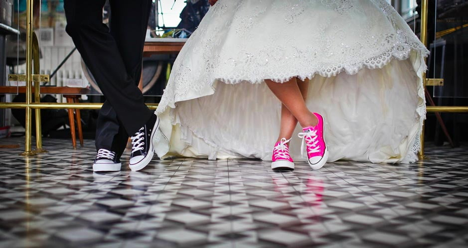 A bride wearing pink baseball shoes under her dress
