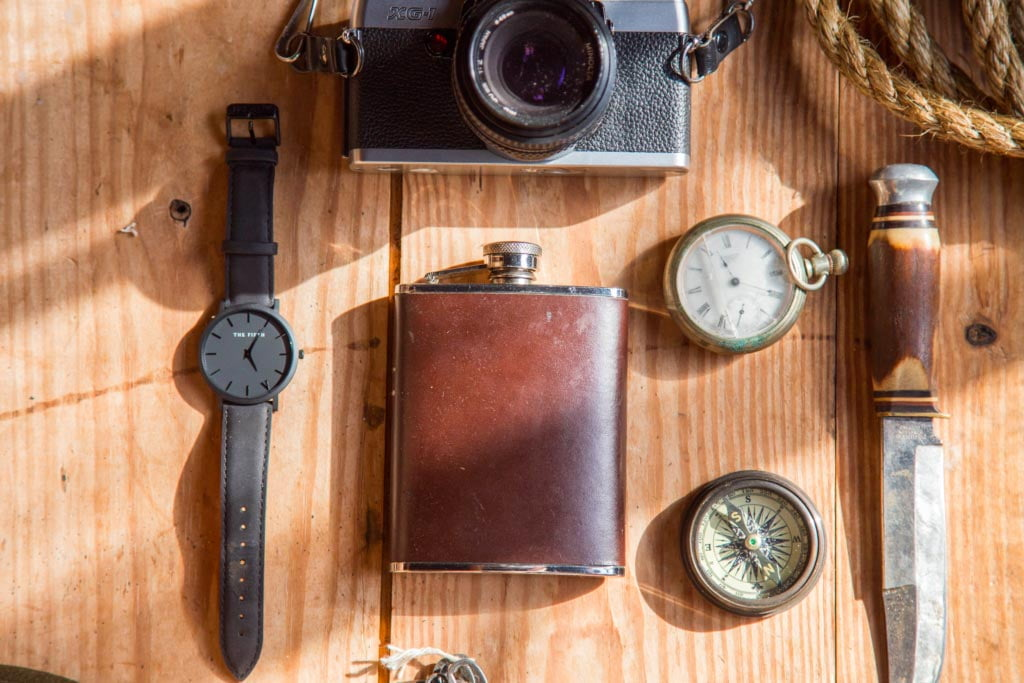 A watch with an old camera and hip flask
